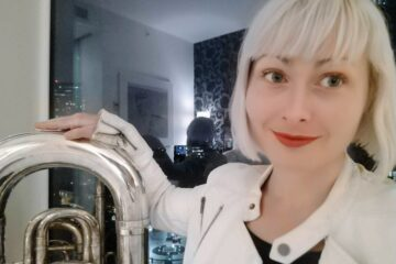 Jessica Aszodi, standing in front of a reflective window, wearing red lipstick, with her arm around a tuba.